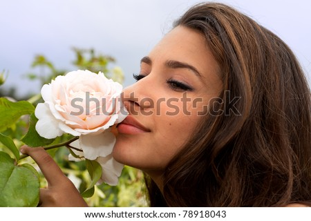 Pretty girl smelling a white rose in the Jardin des Tuilueries in Paris, France. - stock photo