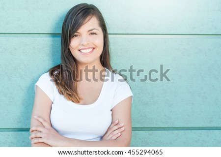 Pretty girl smiling and posing with arms crossed being happy outside on green wall with copy text space - stock photo