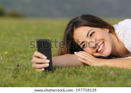 Pretty girl smiling using a smart phone lying on the grass in a park or a mountain - stock photo