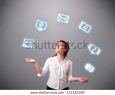 pretty girl standing and juggling with elecrtonic devices icons - stock photo