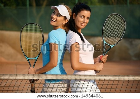 Pretty girl standing on tennis court, smiling, looking at camera.