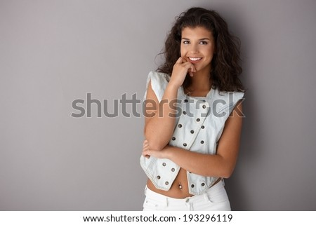 Pretty girl standing over gray background, posing by wall, smiling, looking at camera. - stock photo