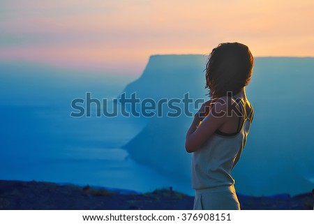 Pretty girl stay on the top of the mountain and see to the horizon with beautiful background. Colorful photo of the natural sunset over the sea.  vertex, cove, miracle, unbelievable, scenery, - stock photo