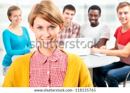 Pretty girl student and her friends on background - stock photo