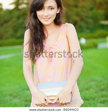 pretty girl-student keeps books in the park for natural background - stock photo