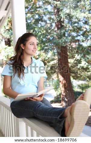 Pretty Girl Studying on Home Porch Reading Book - stock photo