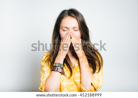 pretty girl surprised closes face with her hands, studio photo, isolated