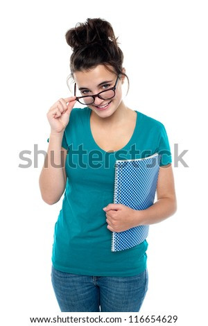 Pretty girl taking off her glasses to watch you closely. Holding spiral notebook