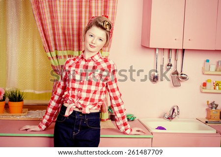 Pretty girl teenager wearing clothes and hair in pin-up style posing on a pink kitchen. Beauty, youth fashion. Pin-up style. - stock photo