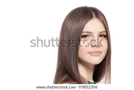 Pretty girl teenager with with long glossy brown hair clean skin looking at camera, isolated on white background in studio closeup - stock photo