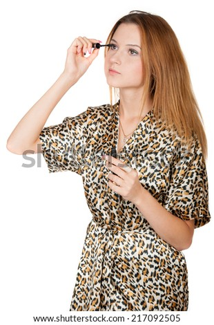 Pretty girl touches up eyelashes on white background - stock photo
