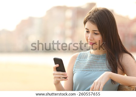Pretty girl using a mobile phone sitting in a bench in an urban park - stock photo