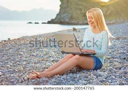 Pretty girl using laptop on the beach. - stock photo