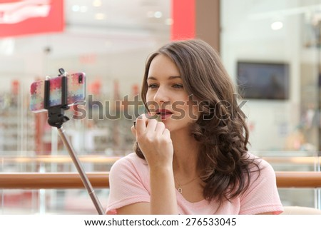 Pretty girl using mobile phone like mirror in shopping mall interior - stock photo