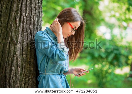 Pretty girl using phone in nature