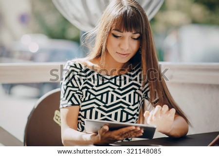 Pretty Girl using tablet phone in cafe - stock photo