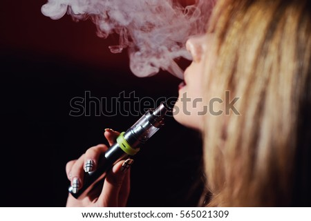 pretty girl viper smoke e-cigarette in a nightclub
