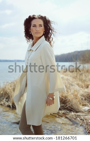 Pretty girl walking by the lake in the spring sunshine - stock photo