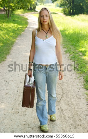 Pretty girl walking on the road with her suitcase - stock photo