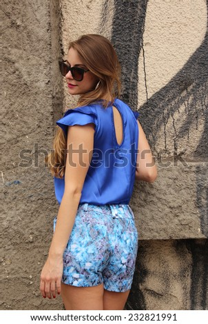 Pretty girl wearing a blue dress posing backside on the wall - stock photo