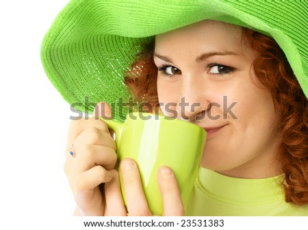 pretty girl wearing a green summer hat has a cup of tea - stock photo