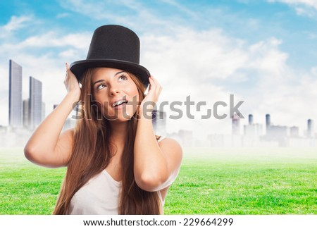 pretty girl wearing a vintage top-hat and thinking about something - stock photo