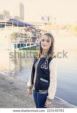 Pretty girl wearing jeans and a school varsity jacket in front of a river paddle boat - stock photo