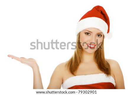 Pretty girl wearing red Christmas hat, holding a hand palm up. Isolated over a white background.