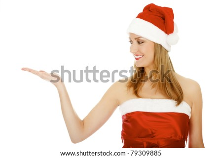 Pretty girl wearing red Christmas hat, holding a hand palm up. Isolated over a white background. - stock photo