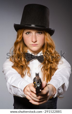 Pretty girl wearing retro hat and holding weapon isolated on gray - stock photo
