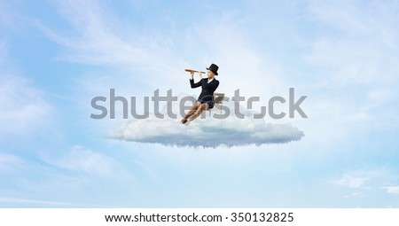 Pretty girl wearing retro hat siting on chair and looking in spyglass - stock photo