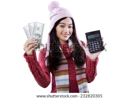 Pretty girl wearing warm clothes and holding money dollars with calculator in studio, isolated on white - stock photo