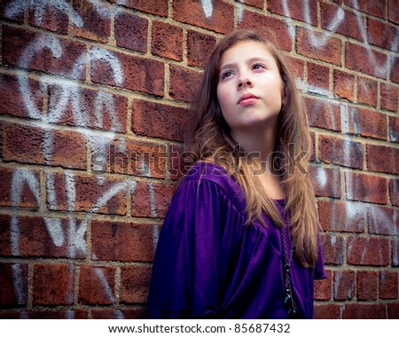 Pretty girl with a faraway look on her face against a grungy, urban brick wall - stock photo