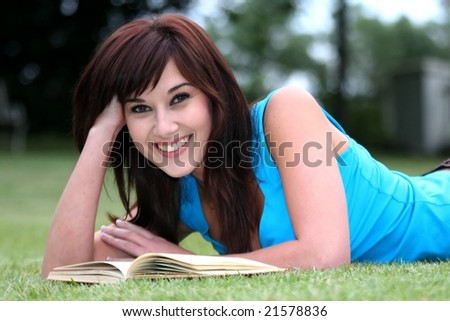 Pretty girl with a smile reading a book outdoors