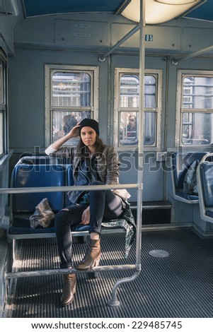 Pretty girl with beanie posing in a metro car