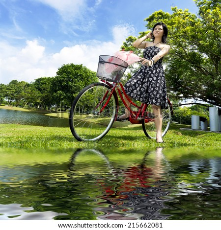 pretty girl with bicycle at the park - stock photo