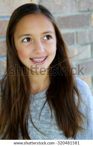 pretty girl with big brown eyes, long brown hair with braces