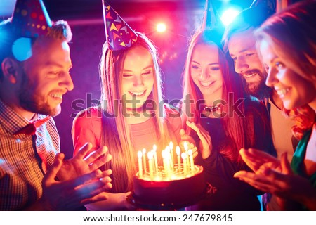 Pretty girl with birthday cake and her friends looking at burning candles at party - stock photo