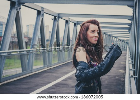 Pretty girl with black leather jacket posing on a bridge