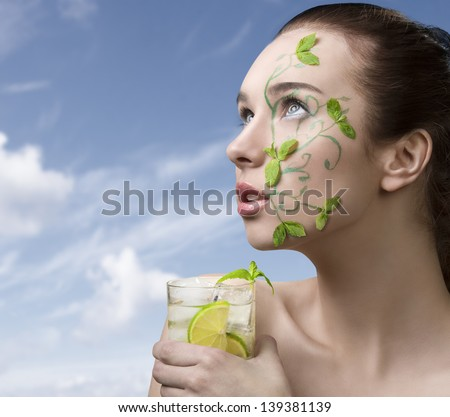 pretty girl with brown hair having creative green make-up with some mint leaves, naked shoulder and mojito cocktail  in the hand - stock photo