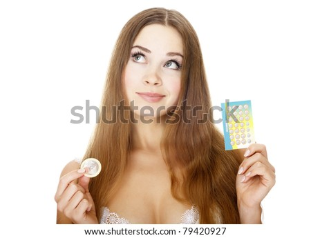 Pretty girl with condom and contraceptive pills. Isolated over a white background. - stock photo