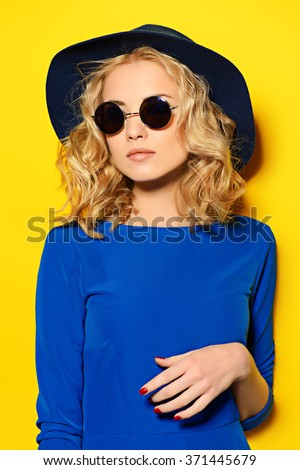 Pretty girl with curly blonde hair wearing bright clothes and sunglasses posing over yellow background. Bright style, fashion. Optics style. - stock photo