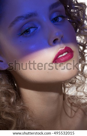 pretty girl with curly hair and blue shadow on the beauty face