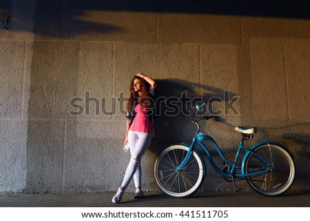 Pretty girl with curly hair is resting at sunset with his bike - stock photo