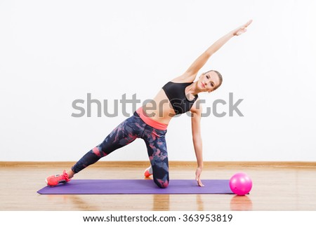 Pretty girl with dark hair wearing pink snickers, dark leggings and black short top doing stretching exercises on mats at gym, fitness, ball on floor, copy space. - stock photo