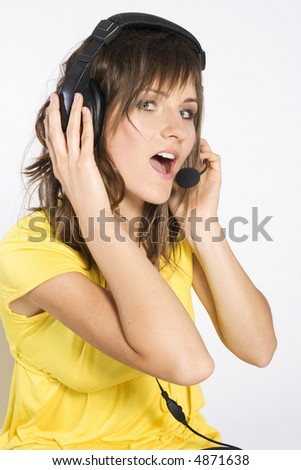 pretty girl with dark hair with headphones and microphone wearing yellow blouse on light background