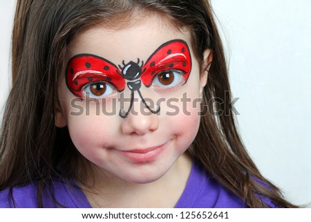 Pretty girl with face painting of a ladybug. - stock photo