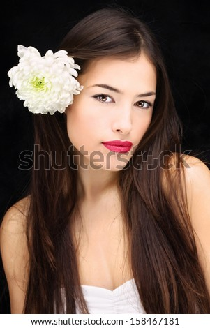Pretty girl with flower in her long hair - stock photo