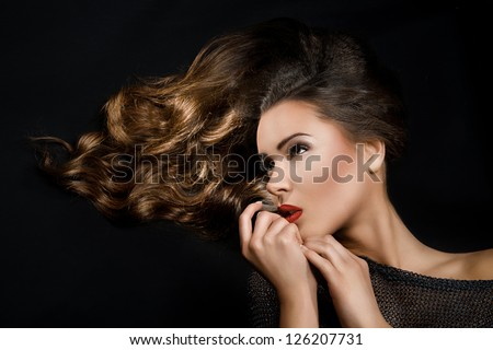 pretty girl with flowing hair and red lipstick turned at right with hand near the chin - stock photo
