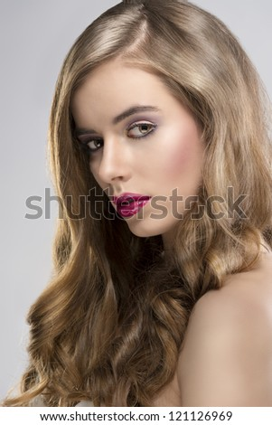 pretty girl with flowing wavy hair and purple make-up, she is turned at right and looks in to the lens - stock photo